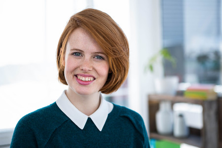 strawberry blonde: smiling hipster business woman, standing in her office Stock Photo