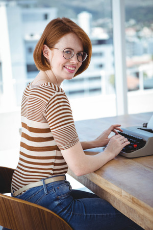 typewrite: hipster typing on a typewrite that is on a wooden desk