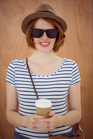 rimmed: smiling hipster woman in a hat and sunglasses, holding a take away coffee against a wooden background