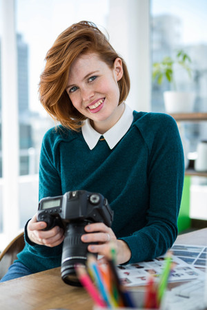 strawberry blonde: smiling hipster photographer, sitting at her desk, looking at her camera