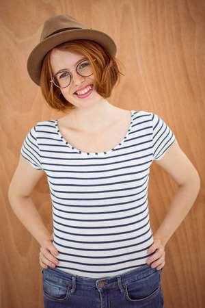 strawberry blonde: smiling hipster woman with her hands on her hips against a wooden background