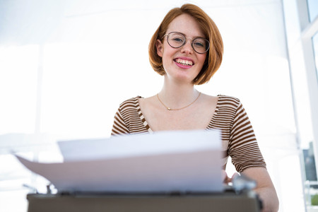 strawberry blonde: smiling hipster woman sitting at a desk, typing on her typewriter