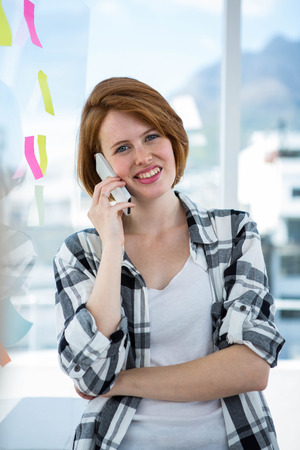phonecall: smiling hipster woman standing in her office making a phonecall Stock Photo