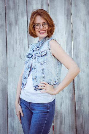 strawberry blonde: smiling hipster woman with her hand on her hip against awooden background