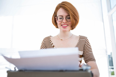 strawberry blonde: hipster typing on a typewrite that is on a wooden desk