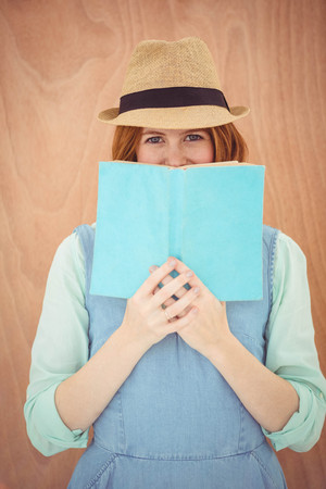 strawberry blonde: smiling hipster woman against aa wooden background, looking out over the top of a book
