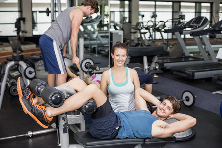crunches: Trainer woman helping man doing her crunches at gym Stock Photo
