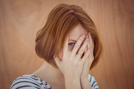 coy: beautiful hipster woman hiding her face on a wooden background