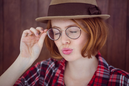 strawberry blonde: hipster woman osing with her eyes closed against a wooden background