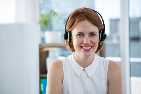 strawberry blonde: smiling hipster business sitting at the desk wearing headphones Stock Photo