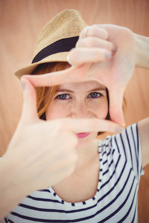 strawberry blonde: blue eyed hipster in a trilby, looking through her hands Stock Photo