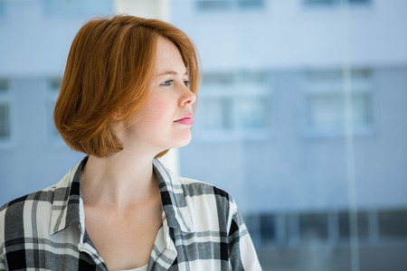 strawberry blonde: Red haired hipster smiling at camera in front of a window Stock Photo