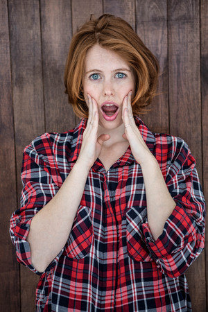 mouthed: shocked hipster woman looking into the camera on a wooden background