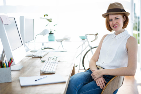 swivel chair: smiling hipster business womansitting at her desk in swivel chair Stock Photo