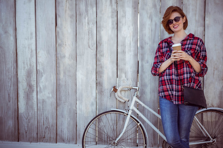strawberry blonde: smiling hipster woman with coffee and a bicycle, standing against a wooden background Stock Photo