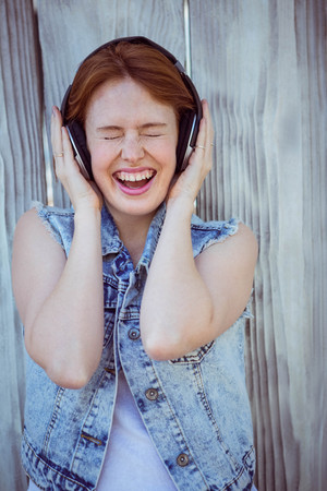 loud music: smiling hipster woman cupping her ears, listening to loud music