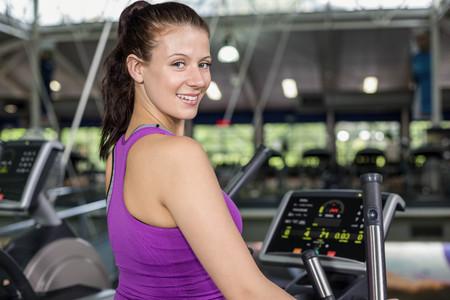 eliptica: Ajustar la mujer de bicicleta el�ptica en el gimnasio Foto de archivo