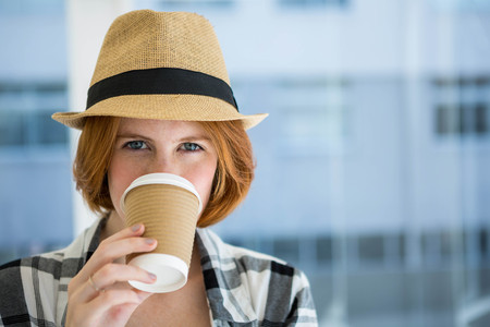 strawberry blonde: Fashion hipster having a coffee in a disposable cup