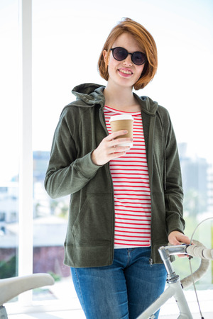 disposable cup: Cute hipster with her bike and disposable cup in front of a window