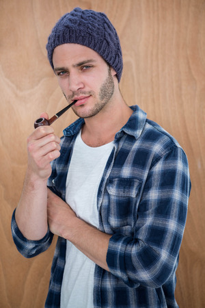 smocking: Handsome hipster smocking a pipe on a wooden background