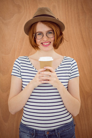 disposable cup: Cute red haired hipster with glasses holding disposable cup on wooden background