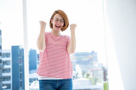 strawberry blonde: Cute red haired hipster with glasses in front of a window Stock Photo