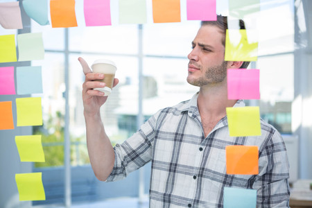 postit: Hipster man pointing at post-it in office