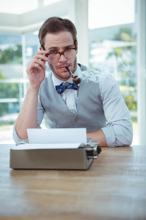 old fashioned: Handsome man using old fashioned typewriter in bright office
