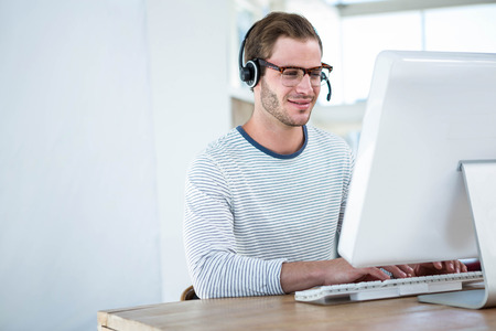 Handsome man working on computer with headset in a bright office