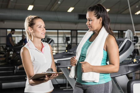 adult  body writing: Trainer talking with woman at the gym
