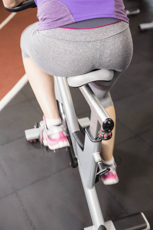 lower section: Pregnant woman using exercise bike at the gym