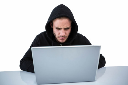 thievery: Handsome man in black hoodie using laptop on white background Stock Photo