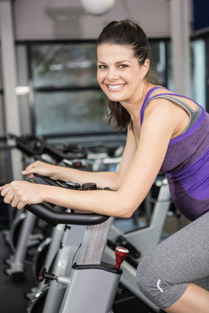 lower section view: Pregnant woman using exercise bike at the gym