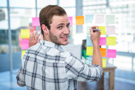 postit: Hipster man writing on post-it in office