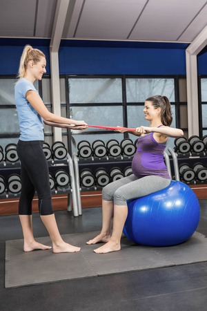 belly band: Trainer and pregnant woman using a resistance band at a gym