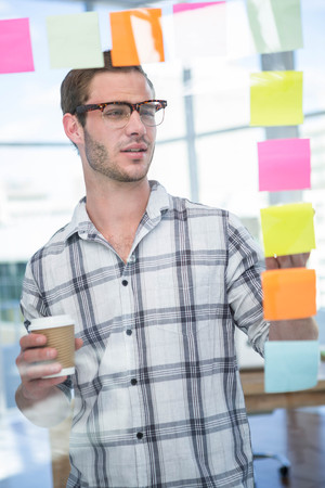 postit: Hipster man looking at post-it in office