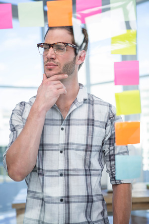 postit: Thoughtful hipster man with post-it in office