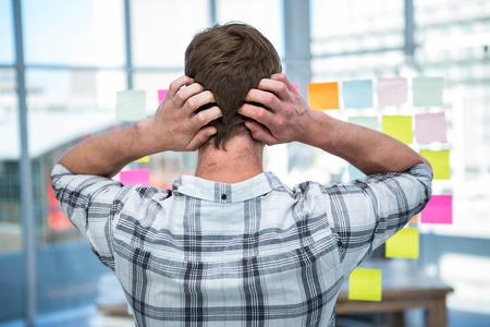 postit: Worried hipster man in front of post-it in office