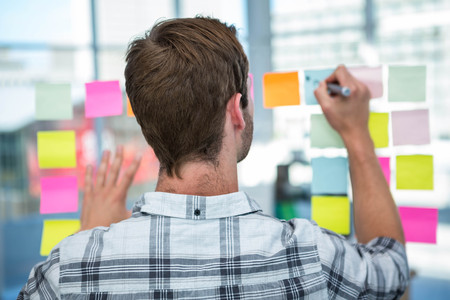 Hipster man writing on post-it in office