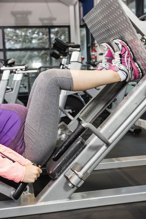 high def: Pregnant woman using weight machine at the gym Stock Photo