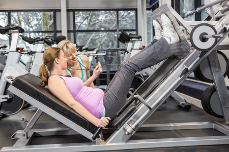 motivating: Trainer motivating pregnant woman while using leg press at the gym
