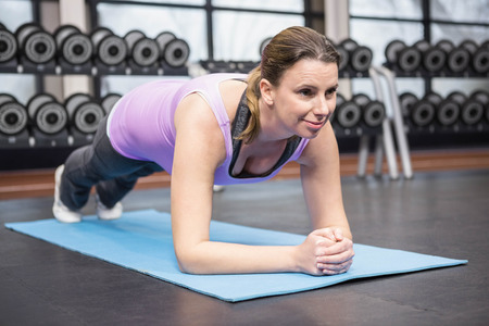 planking: Determined woman planking on the mat at the gym
