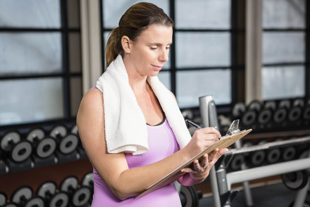 adult  body writing: Pregnant woman writing on clipboard at the gym