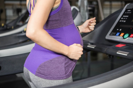 Střední část těhotná žena běžící na běžeckém pásu v posilovně