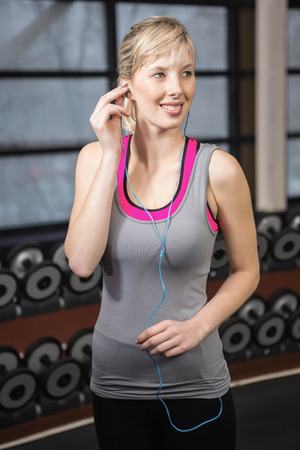 Fit blonde listening to music at the gym Stock Photo