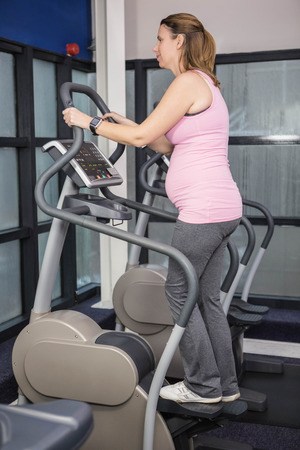 crosstrainer: Pregnant woman on crosstrainer at the gym Stock Photo