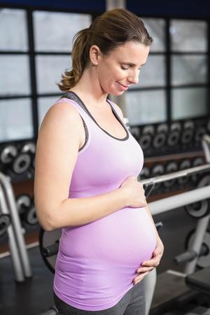ropa deportiva: La mujer embarazada en ropa de deportes en el gimnasio