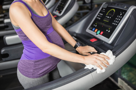 mid section: Mid section of pregnant woman cleaning treadmill at the gym