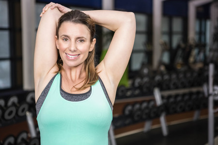middleaged: Smiling brunette stretching her arms at the gym