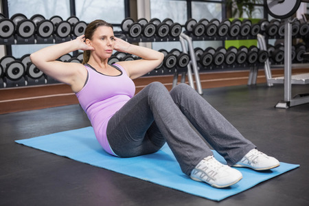 crunches: Woman doing abdominal crunches on mat at the gym